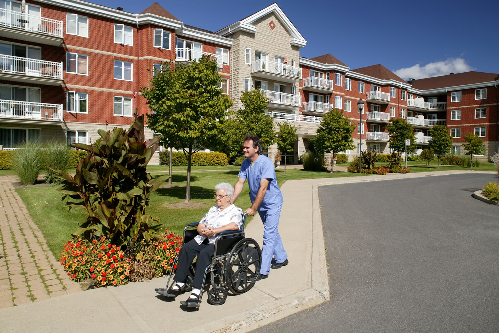 senior citizen in wheel chair with nurse out front of assisted living facility
